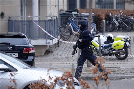 "An armed security officer runs down a street near a venue after shots were fired where an event titled ""Art, blasphemy and the freedom of expression"" was being held in Copenhagen, Saturday, Feb. 14, 2015. Danish media say several shots have been fired at a cafe in Copenhagen where a meeting about freedom of speech was being held, organized by Swedish artist Lars Vilks, who has faced numerous threats for caricaturing the Prophet Muhammad in 2007. (AP Photo/Polfoto, Kenneth Meyer"