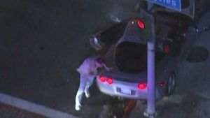 Police surrounded a silver Corvette in downtown Los Angeles after a lengthy pursuit. The driver was fatally shot when he exited the vehicle on Dec. 13, 2013. (Credit: KTLA)