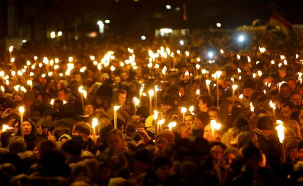 People hold candles during a memorial service is held for those killed on Saturday by a 22-year-old gunman, in Copenhagen