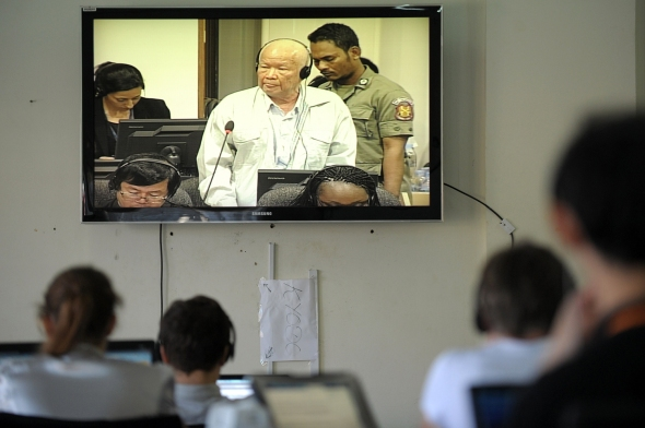 Cambodian and international journalists watch a live video feed showing former Khmer Rouge leader head of state Khieu Samphan (C) during a hearing for his trial at the Extraordinary Chamber in the Courts of Cambodia (ECCC) in Phnom Penh on January 8, 2015. Cambodia's UN-backed court on January 8, resumed the genocide trial of two ex-Khmer Rouge leaders over the mass murder of Vietnamese people and ethnic Muslims, forced marriage and rape in late 1970s.     AFP PHOTO / TANG CHHIN SOTHY        (Photo credit should read TANG CHHIN SOTHY/AFP/Getty Images)