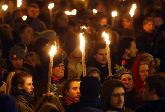 People hold candles during a memorial service held for those killed on Saturday by a 22-year-old gunman, in Copenhagen February 16, 2015.  REUTERS/Leonhard Foeger
