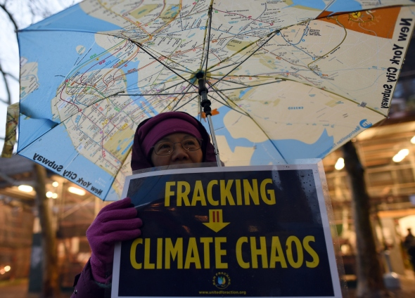 A woman holds an anti-fracking sign as a group of demonstrators gather for a rally for a Global Climate Treaty December 10, 2014 near the United Nations in New York. New Yorkers gathered to demand that world governments address the serious threat global warming poses to human rights. This event coincides with a UN meeting in Lima, Peru, a part of the 2014-15 negotiations for a global climate treaty. AFP PHOTO/DON EMMERT/Getty