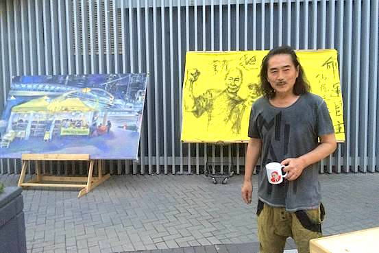 New York-based artist Miso stands in front of some of his paintings near the Occupy protest site in Hong Kong's Admiralty neighborhood. Isabella Steger/The Wall Street Journal