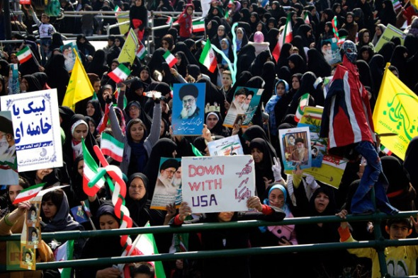 "Iranian demonstrators hold anti-US slogans and portraits of supreme leader, Ayatollah Ali Khamenei during a rally in Tehran's Azadi Square (Freedom Square) to mark the 34th anniversary of the Islamic revolution on February 10, 2013. Hundreds of thousands of people marched in Tehran and other cities chanting ""Death to America"" and ""Death to Israel"" as Iran celebrated the anniversary of the ousting of the US-backed shah. AFP PHOTO / BEHROUZ MEHRI"