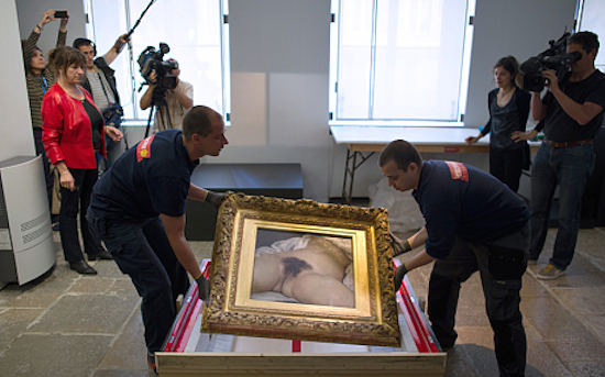 Two hauliers prepare to install the Gustave Courbet's canvas 'L'origine du monde' (The origin of the world) at the Courbet museum (AFP)