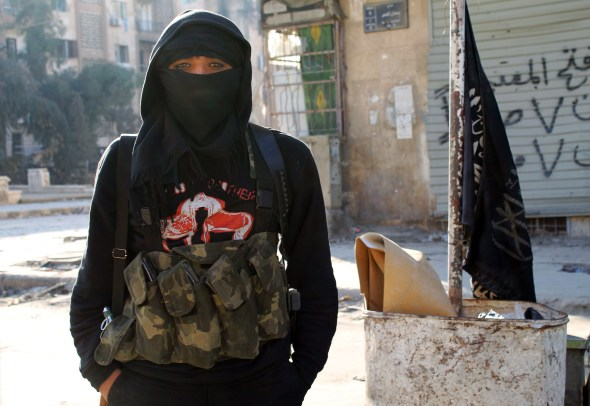 A member of jihadist group Al-Nusra Front stands in a street of the northern Syrian city of Aleppo on January 11, 2014. Fighting pitting the Islamic State of Iraq and the Levant (ISIL) against other rebel groups -- including Al-Nusra Front, which is also linked to Al-Qaeda but is seen as more moderate -- broke out in Syria last week. AFP PHOTO / BARAA AL-HALABI