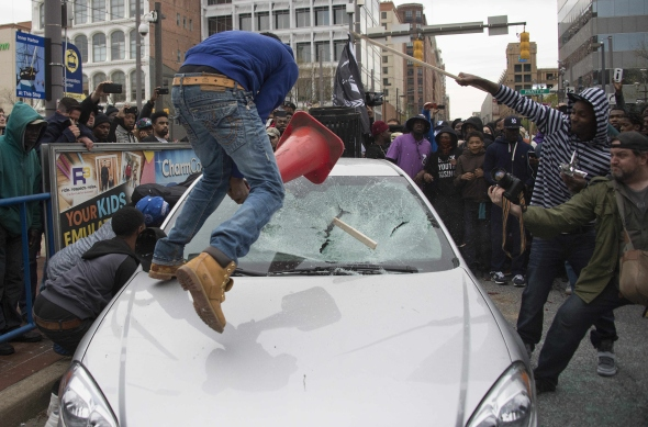 Demonstrators destroy the windshield of a Baltimore Police car as they protest the death Freddie Gray, an African American man who died of spinal cord injuries in police custody, in Baltimore, Maryland, April 25, 2015. Protesters returned to Baltimore's streets Saturday to vent outrage over the death of Gray. JIM WATSON/AFP/Getty Images