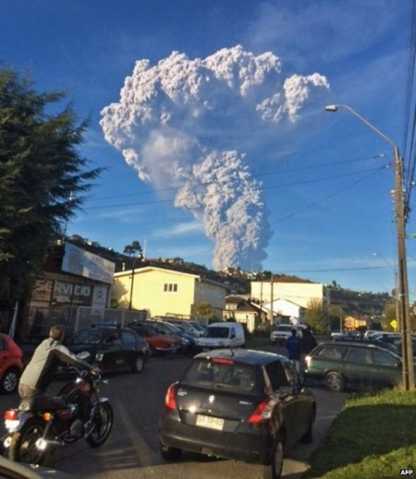 People in the town of Puerto Varas look on at the volcano's huge ash cloud