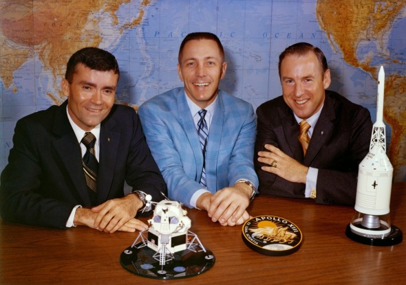 Astronauts Fred Haise (left), Jack Swigert and James Lovell pose with the Apollo 13 patch and spacecraft models the day before launch. Image Credit: NASA.