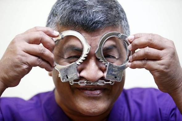 Malaysian political cartoonist Zulkiflee Anwar Ulhaque, better known as Zunar, played with fake handcuffs during his court case in Kuala Lumpur on Friday. PHOTO: EUROPEAN PRESSPHOTO AGENCY