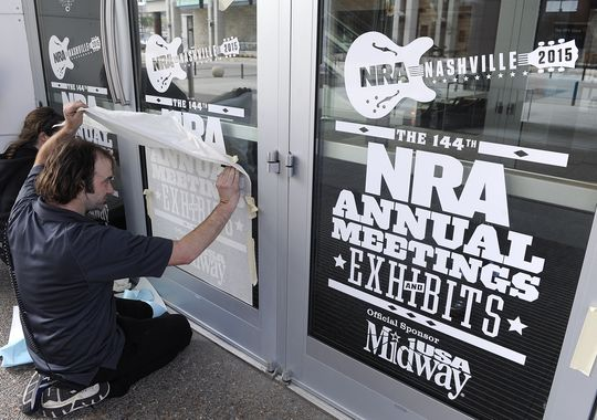 Nick Faddy with CPR Signs places a NRA Convention sign on the doors of Music City Center for this week's National Rifle Association convetntion, which will bring an estimated 70,000 people. (Photo: Shelley Mays / The Tennessean)