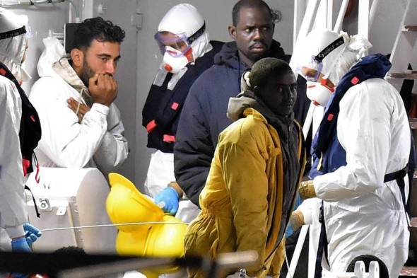 Tunisian skipper Mohammed Ali Malek, left, seen Monday on board an Italian Coast Guard ship at the port of Catania, was detained on suspicion of multiple counts of murder. Photo: Tullio M. Puglia/Getty Images
