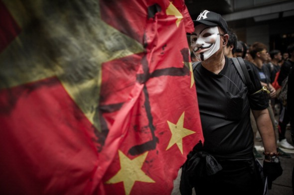 A man wears a mask of the Anonymous hacker group as he and other people take part in a protest for the cause of late Chinese dissident Li Wangyang in Hong Kong on June 10, 2012. Li, 62, who spent 22 years in jail for his role in the Tiananmen democracy protests died in allegedly suspicious circumstances in his hospital ward in central China's Hunan province on June 6 by his sister and brother-in-law. AFP PHOTO / Philippe Lopez (Photo credit should read PHILIPPE LOPEZ/AFP/GettyImages)