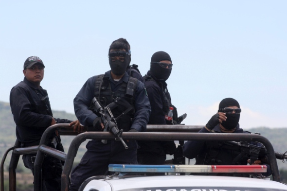 Federal police officers leave the ranch where gunmen took cover during an intense gun battle with the police, along the Jalisco-Michoacan highway in Vista Hermosa, Michoacan State, on May 22, 2015. At least 37 people were killed in the gunfight in Mexico's troubled western state of Michoacan, in one of the bloodiest clashes in the country's drug war. Two police officers also died in the shootout in the municipality of Tanhuato, near the border with Jalisco state, a federal government official told AFP. Michoacan and Jalisco have endured some of the worst violence in a drug war that began to escalate in 2006, when the government deployed troops to combat cartels. More than 80,000 have been killed and another 22,000 gone missing nationwide in the past nine years.  AFP PHOTO / HECTOR GUERRERO        (Photo credit should read HECTOR GUERRERO/AFP/Getty Images)