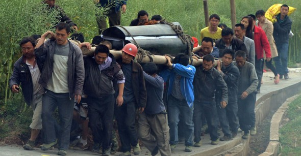 Villagers carry the coffin of a man killed after a magnitude 7.0 earthquake hit Lushan, Sichuan Province on April 22, 2013.  Clogged roads, debris and landslides impeded rescuers as they battled to find survivors of a powerful earthquake in mountainous southwest China that has left at least 188 dead.                  AFP PHOTO/Mark RALSTON        (Photo credit should read MARK RALSTON/AFP/Getty Images)