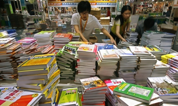 Exhibitors arrange books at a booth at the annual Book Fair in Hong Kong Tuesday, July 18, 2006. Over 10,000 titles and showcased by 430 exhibitors, the Hong Kong Book Fair will open from July 19 to July 24. (AP Photo/Vincent Yu)