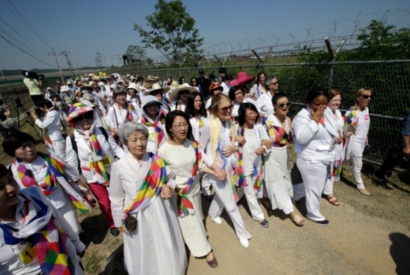 U.S. activist Gloria Steinem, sixth right in front, two Nobel Peace Prize laureates Mairead Maguire, from Northern Ireland, second from right, Leymah Gbowee, from Liberia, third from right, and other activists march to the Imjingak Pavilion with South Korean activists along the military wire fences near the border village of Panmunjom, in Paju, north of Seoul, South Korea, Sunday, May 24, 2015. International women activists including Steinem and two Nobel Peace laureates on Sunday were denied an attempt to walk across the Demilitarized Zone dividing North and South Korea, but were allowed to cross by bus and complete what one of them called a landmark peace event. (AP Photo/Lee Jin-man)