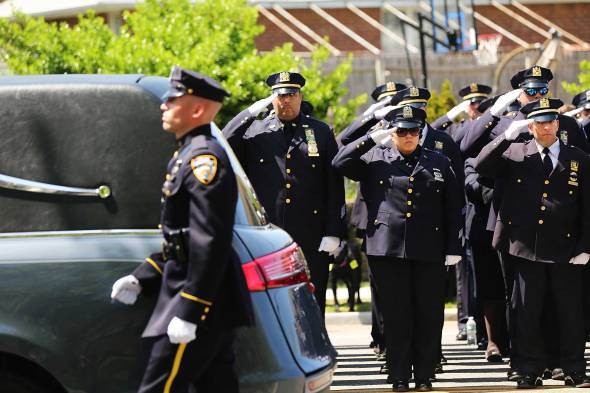 SEAFORD, NY - MAY 08: The hearse carrying the casket for fallen New York City police officer Brian Moore leaves a Long Island church on May 8, 2015 in Seaford, New York. Officer Moore died last Monday after being shot in the head while on duty two days earlier in Queens. The 25-year-old officer and his partner stopped a man suspected of carrying a handgun when the man opened fire on them. As many as 30,000 police officers from across the United States payed their respects at the Long Island funeral. (Photo by Spencer Platt/Getty Images)