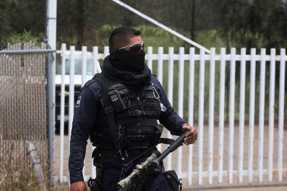 A federal police officer stands guard outside the ranch in Michoacan state where more than 40 people were killed in Friday's shootout. (Hector Guerrero/AFP/Getty Images)