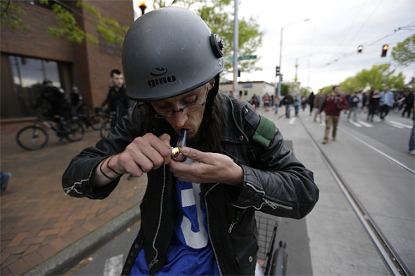An anti-capitalist protester smokes marijuana as he takes part in a May Day demonstration, Friday, May 1, 2015 in downtown Seattle. (AP Photo/Ted S. Warren)
