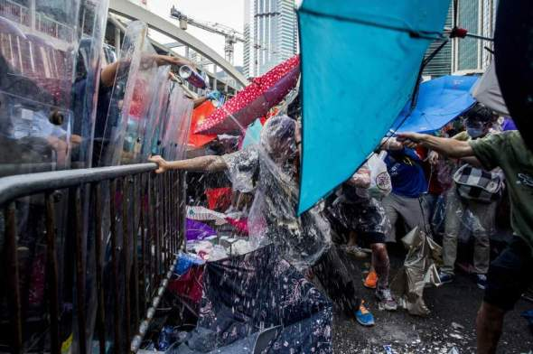 Pro-democracy demonstrators are sprayed with pepper spray during clashes with police officers during a rally near the Hong Kong government headquarters on September 28, 2014. Police fired tear gas as tens of thousands of pro-democracy demonstrators brought parts of central Hong Kong to a standstill on September 28, in a dramatic escalation of protests that have gripped the semi-autonomous Chinese city for days. AFP PHOTO / XAUME OLLEROS        (Photo credit should read XAUME OLLEROS/AFP/Getty Images)