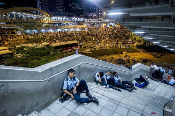 Policemen rest following pro-democracy protests in Hong Kong on September 29, 2014.  Police fired tear gas as tens of thousands of pro-democracy demonstrators brought parts of central Hong Kong to a standstill in a dramatic escalation of protests that have gripped the semi-autonomous Chinese city for days.    AFP PHOTO / XAUME OLLEROS        (Photo credit should read XAUME OLLEROS/AFP/Getty Images)