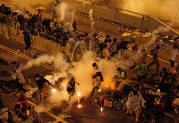 Riot police use tear gas against protesters after thousands of people blocked a main road at the financial central district in Hong Kong, Sunday, Sept. 28, 2014. Hong Kong police used tear gas on Sunday and warned of further measures as they tried to clear thousands of pro-democracy protesters gathered outside government headquarters in a challenge to Beijing over its decision to restrict democratic reforms for the city. (AP Photo) HONG KONG OUT