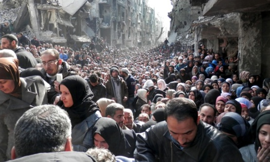 In this Jan. 31, 2014, file photo released by the United Nations Relief and Works Agency for Palestine Refugees in the Near East (UNRWA), residents of the besieged Yarmouk refugee camp near Damascus, Syria, queue to receive food supplies. Conditions in the camp have deteriorated since Islamic State militants muscled their way into it in early April 2015. The militants are trying to consolidate their hold on the camp. (AP Photo/UNRWA, File)