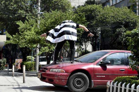 As he goes about his mission Peatonito wears a wrestling mask adorned with a pedestrian symbol and a striped cape (sewn by his grandma) adorned with the black and white stripes of a pedestrian crossing (AFP Photo/Yuri Cortez)