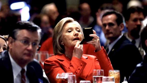 U.S. Democratic presidential candidate Hillary Clinton adjusts her make-up before speaking at the Iowa Democratic Party's Hall of Fame dinner in Cedar Rapids