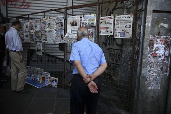 A man reads newspaper headlines in Athens, Greece July 8, 2015.  REUTERS/Alkis Konstantinidis