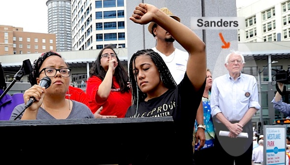 Marissa Johnson, left, speaks as Mara Jacqueline Willaford holds her fist overhead and Democratic presidential candidate Sen. Bernie Sanders, I-Vt., stands nearby as the two women take over the microphone at a rally Saturday, Aug. 8, 2015, in downtown Seattle. The women, co-founders of the Seattle chapter of Black Lives Matter, took over the microphone and refused to relinquish it. Sanders eventually left the stage without speaking and instead waded into the crowd to greet supporters. (AP Photo/Elaine Thompson)