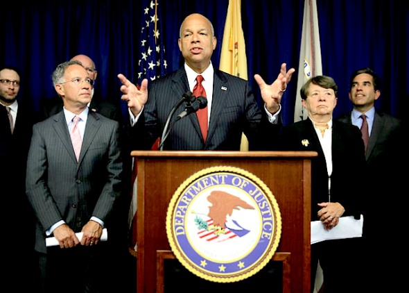 United States Secretary of Homeland Security Jeh Johnson, center, speaks during a news conference in Newark, N.J., Tuesday, Aug. 11, 2015. An international group of hackers and stock traders made $30 million by breaking into the computers of newswire services that put out corporate press releases and trading on the information before it was made public, federal prosecutors said Tuesday. (AP Photo/Seth Wenig)