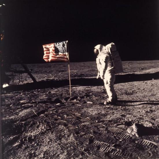 "In this July 20, 1969 file photo, astronaut Edwin E. ""Buzz"" Aldrin Jr. stands next to a U.S. flag planted on the moon during the Apollo 11 mission. Aldrin and Neil Armstrong were the first men to walk on the lunar surface. During a ceremony in Melbourne, Fla. on Thursday, Aug. 27, 2015, Aldrin announced he is teaming up with the Florida Institute of Technology to develop ""a master plan"" for colonizing Mars within 25 years. (Neil A. Armstrong/NASA via AP)"