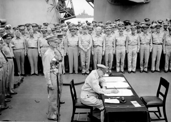 Gen. Douglas MacArthur signs as Supreme Allied Commander during formal surrender ceremonies on the USS MISSOURI in Tokyo Bay. Behind Gen. MacArthur are Lt. Gen. Jonathan Wainwright and Lt. Gen. A. E. Percival, September 2, 1945