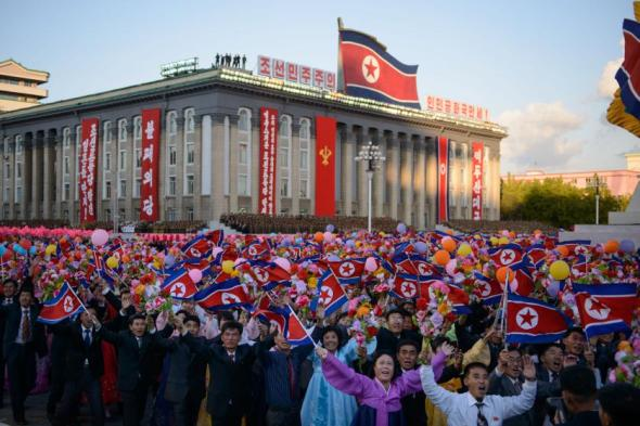 Participants wave flowers towards North Korean leader Kim Jong-Un (not pictured) as they pass through Kim Il-Sung square during a mass military parade in Pyongyang on October 10, 2015. North Korea was marking the 70th anniversary of its ruling Workers' Party. AFP PHOTO / Ed Jones (Photo credit should read ED JONES/AFP/Getty Images)
