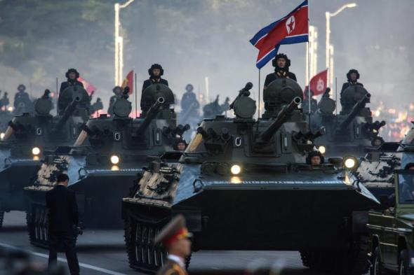 North Korean soldiers ride atop armoured vehicles during a mass military parade at Kim Il-Sung square in Pyongyang on October 10, 2015. North Korea was marking the 70th anniversary of its ruling Workers' Party. AFP PHOTO / Ed Jones (Photo credit should read ED JONES/AFP/Getty Images)