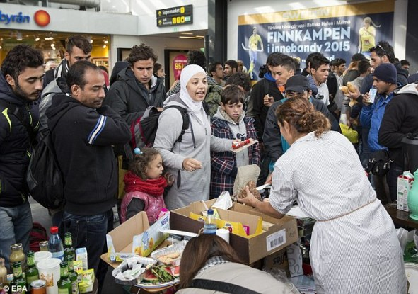 Volunteers hand out supplies to refugees at Malmo Train Station in Sweden. It is expected that Sweden will take in around 190,000 migrants by the end of 2015