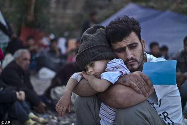 A Syrian refugee child sleeps in his father's arms while waiting at a resting point to board a bus, after arriving on a dinghy from the Turkish coast to the northeastern Greek island of Lesbos