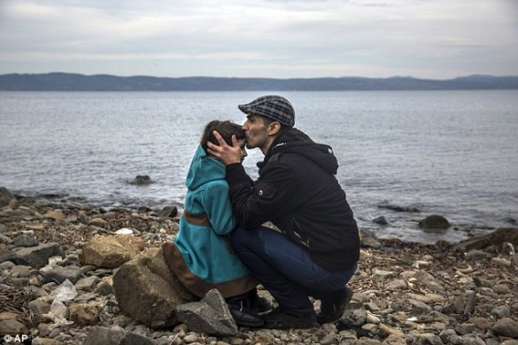 A Syrian man kisses his daughter shortly after disembarking from a dinghy at a beach on the Greek island of Lesbos after crossing the Aegean sea from the Turkish coast
