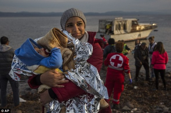 Rescued: A Syrian woman holds her baby after their arrival on a small boat from the Turkish coast on the northeastern Greek island of Lesbos
