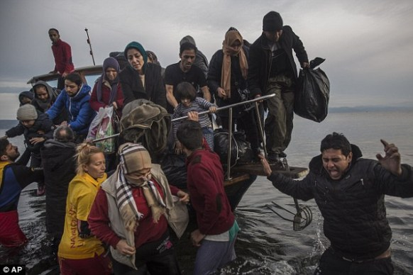 Growing problem: Migrants and refugees disembark from a small boat after crossing from the Turkish coast on the northeastern Greek island of Lesbos today