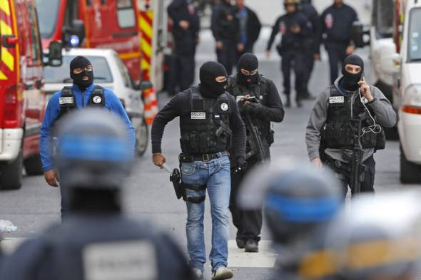 SAMU members and French police participate in a raid in Saint-Denis. ETIENNE LAURENT/EUROPEAN PRESSPHOTO AGENCY Hooded police officers walked on a street in Saint-Denis Wednesday. A woman wearing an explosive suicide vest blew herself up as heavily armed police tried to storm a suburban Paris apartment where the suspected mastermind of last week's attacks was believed to be holed up, police said. PETER DEJONG/ASSOCIATED PRESS