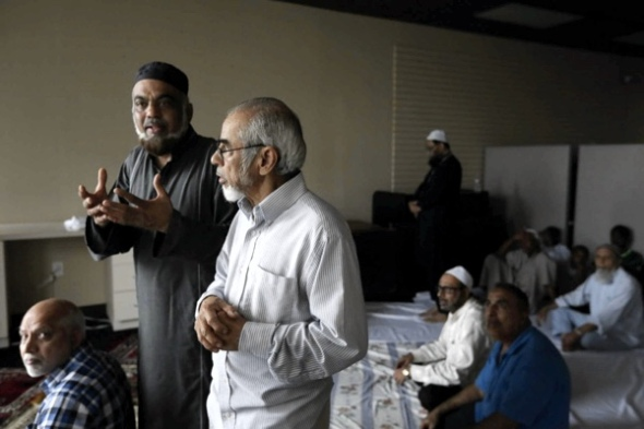 Mohammed Suleman, left, and Shezad Chatriwala, talk before prayers at a makeshift location near the damaged Savoy Mosque Saturday, Dec. 26, 2015, in Houston. A two-alarm fire damaged the mosque Christmas day, and authorities are investigating the cause. Photo: Jon Shapley, Houston Chronicle