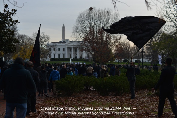 Anwar Al-Zaidy, of Virginia, right, waves a black flag Sunday during a Shiite Muslim rally against terrorism in front of the White House, held just hours before President Obama was to address the nation about the shootings in San Bernardino, California. The shootings are being investigated as terrorism, and possibly linked to the Islamic State in Iraq and Syria, which is supported mainly by Sunni Muslims.