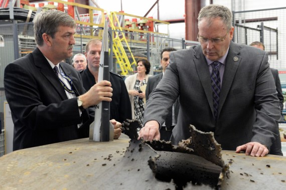 Deputy Secretary of Defense Robert Work, right, views the hole made in a steel plate by a railgun projectile during testing last year at a top-secret Naval facility in Dahlgren, Va.