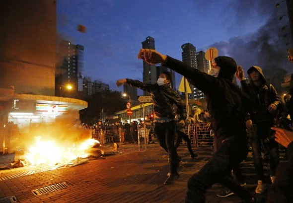 Rioters throw bricks at police in Hong Kong in February after local authorities tried to prevent street food sellers from operating. (Kin Cheung/AP)
