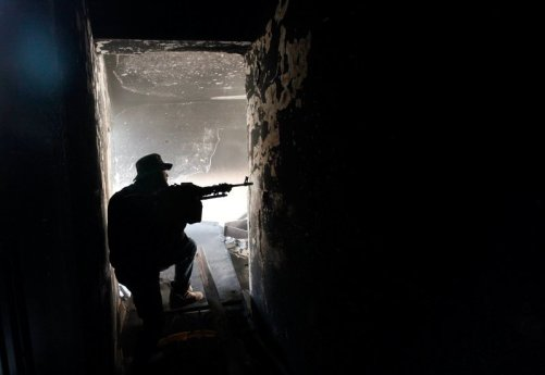 A fighter of Libyan forces allied with the U.N.-backed government aims his weapon as he takes up position inside a ruined house at the front line of fighting with Islamic State militants in Ghiza Bahriya district in Sirte, Libya November 9, 2016. REUTERS/Ismail Zitouny