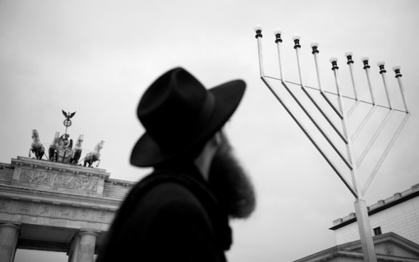 Rabbi Shmuel Segal of the Jewish education centre looks up at the Chanukkah lights in front of Brandenburg Gate in Berlin, December 20, 2011. Chanukkah, also known as the Festival of Lights, is an eight-day Jewish holiday commemorating the re-dedication of the Holy Temple (the Second Temple) in Jerusalem at the time of the Maccabean Revolt of the 2nd century BCE. Hanukkah is observed for eight nights and days, starting on the 25th day of Kislev according to the Hebrew calendar, which may occur at any time from late November to late December in the Gregorian calendar.    AFP PHOTO / ODD ANDERSEN (Photo credit should read ODD ANDERSEN/AFP/Getty Images)