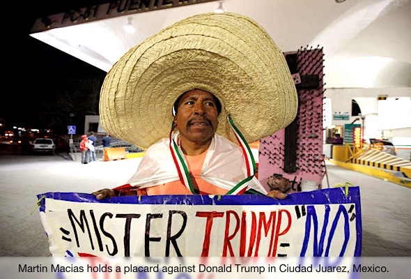 Martin Macias holds a placard against U.S. Republican presidential nominee Donald Trump while standing at Paso del Norte international border crossing bridge in Ciudad Juarez, Mexico, November 8, 2016. REUTERS/Jose Luis Gonzalez